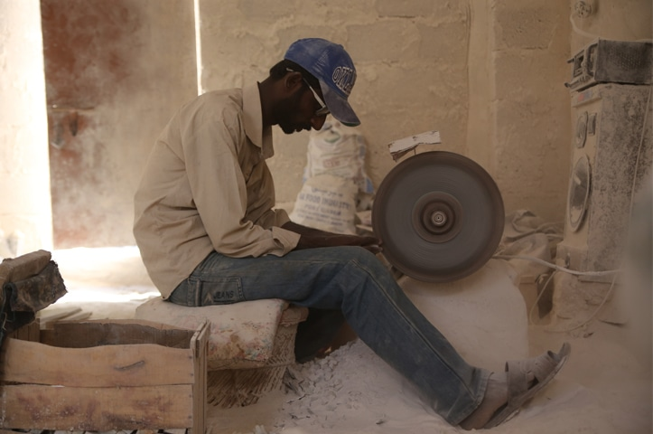 Artisan Ghulam cuts and shapes a marble block