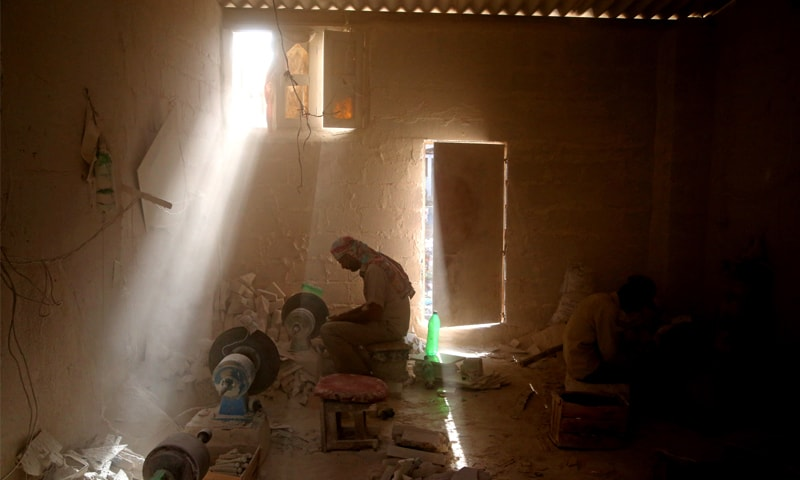 As the dust floats in his face, Ramzan shapes a marble block into a decorative item   Photos by Basil Andrews