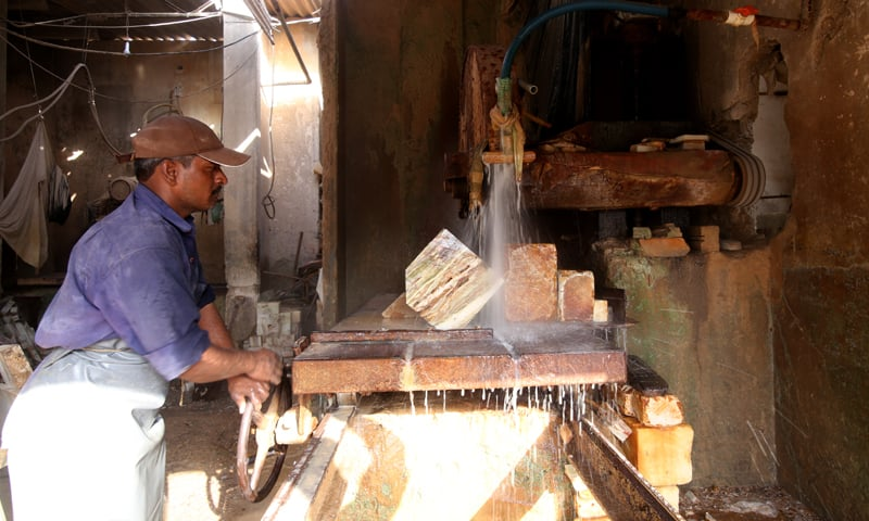 A smaller marble block is brought to a workshop in Pak Colony for washing and cutting to size. The block is first loaded onto a stone cutting machine