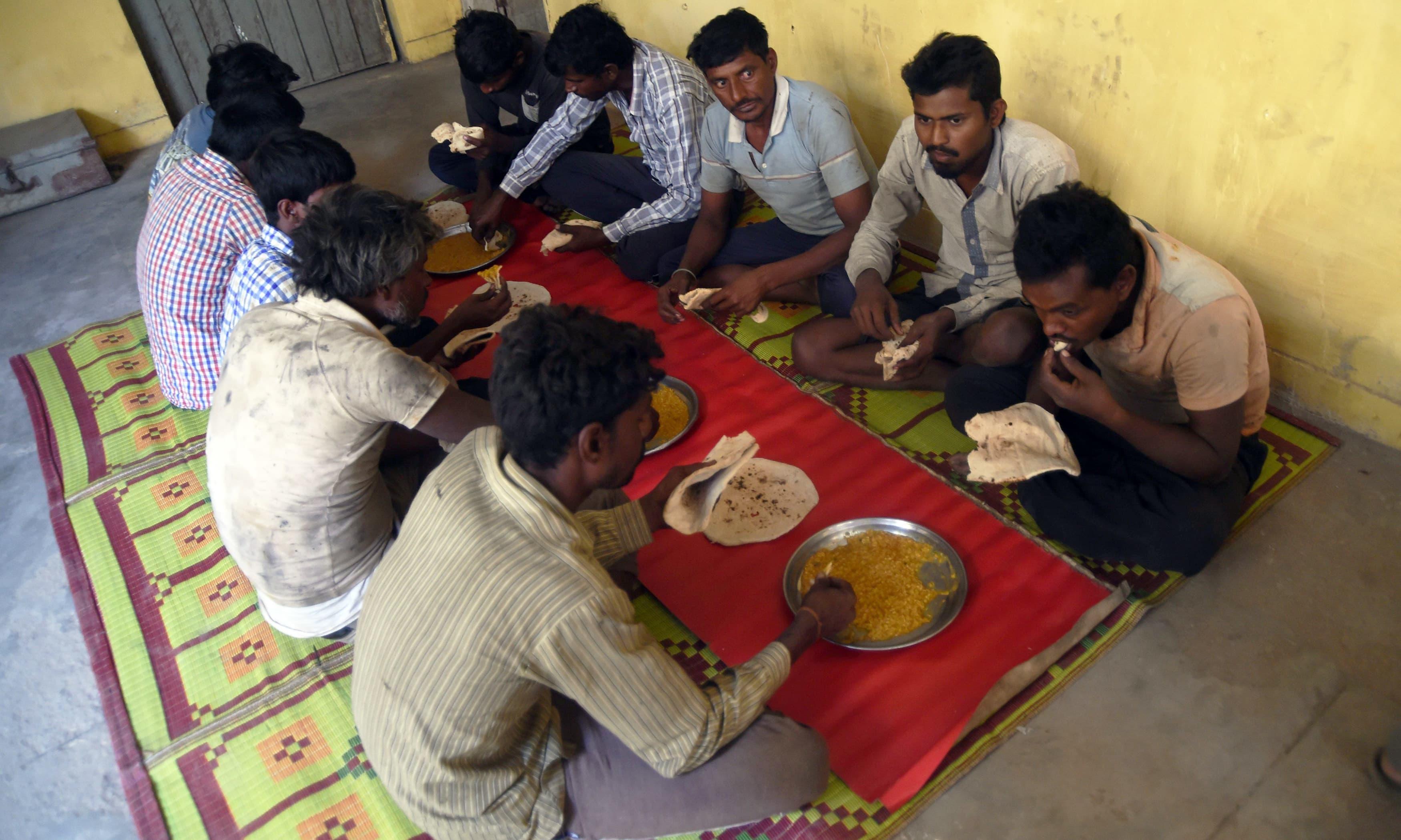 Arrested Indian fishermen eat lunch at a police station in Karachi. —AFP