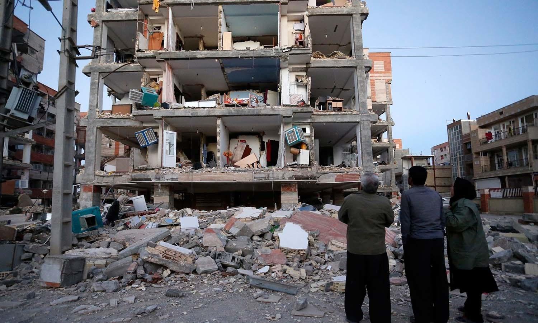 زلزلے سے متاثرہ افراد تباہ شدہ عمارت کو دیکھ رہے ہیں — فوٹو: اے پی