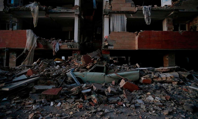 ایران کے صوبے کرمان شاہ میں  تباہ حال عمارت کے ملبے میں گاڑی دبی ہوئی ہے — فوٹو: اے ایف پی