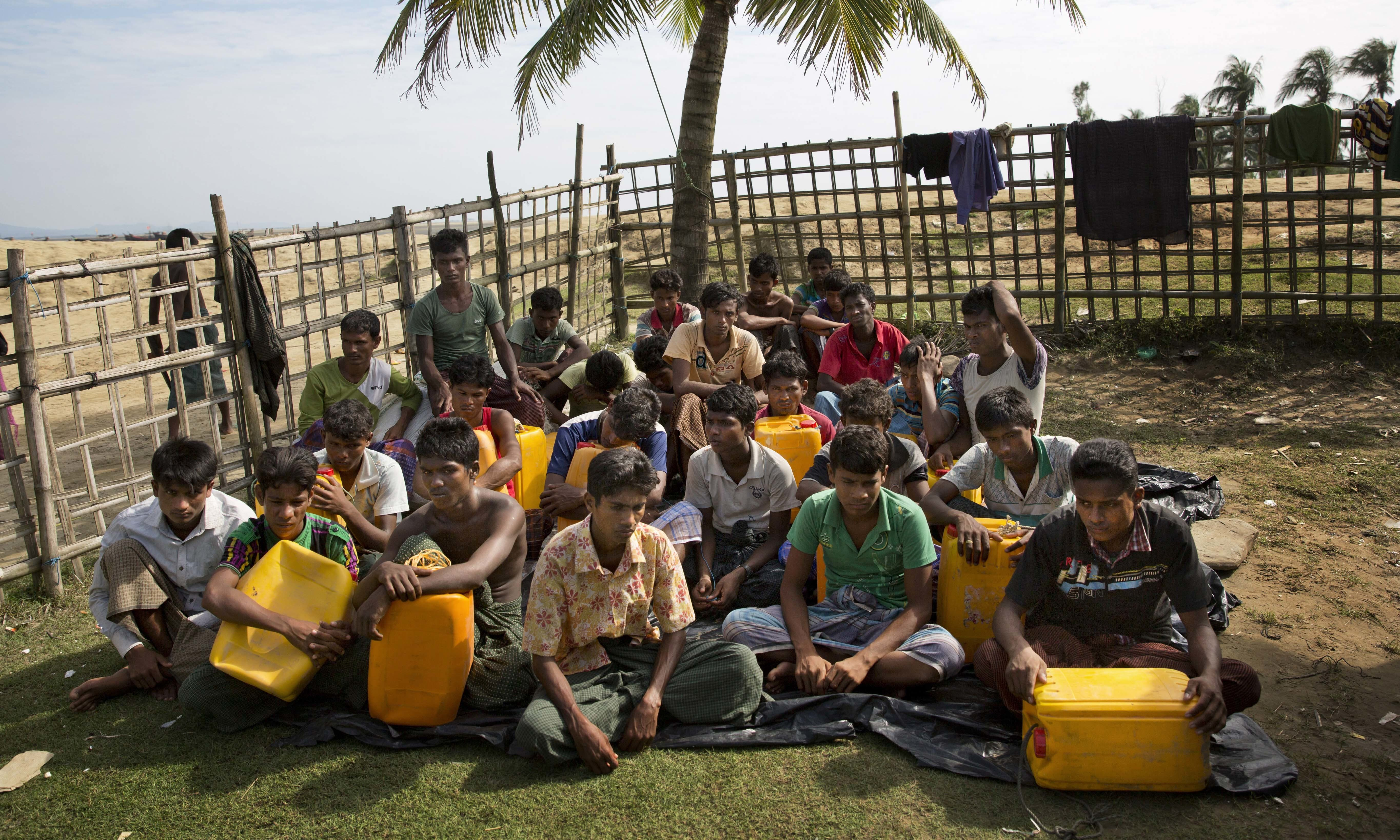 In this Nov. 4, 2017, photo, newly arrived Rohingya Muslims with yellow plastic drums they used to aid flotation while crossing the Naf river wait in Shah Porir Dwip to be transferred to a refugee camp in Cox's Bazar, Bangladesh. The Naf river is a natural border between Myanmar and Bangladesh. —AP