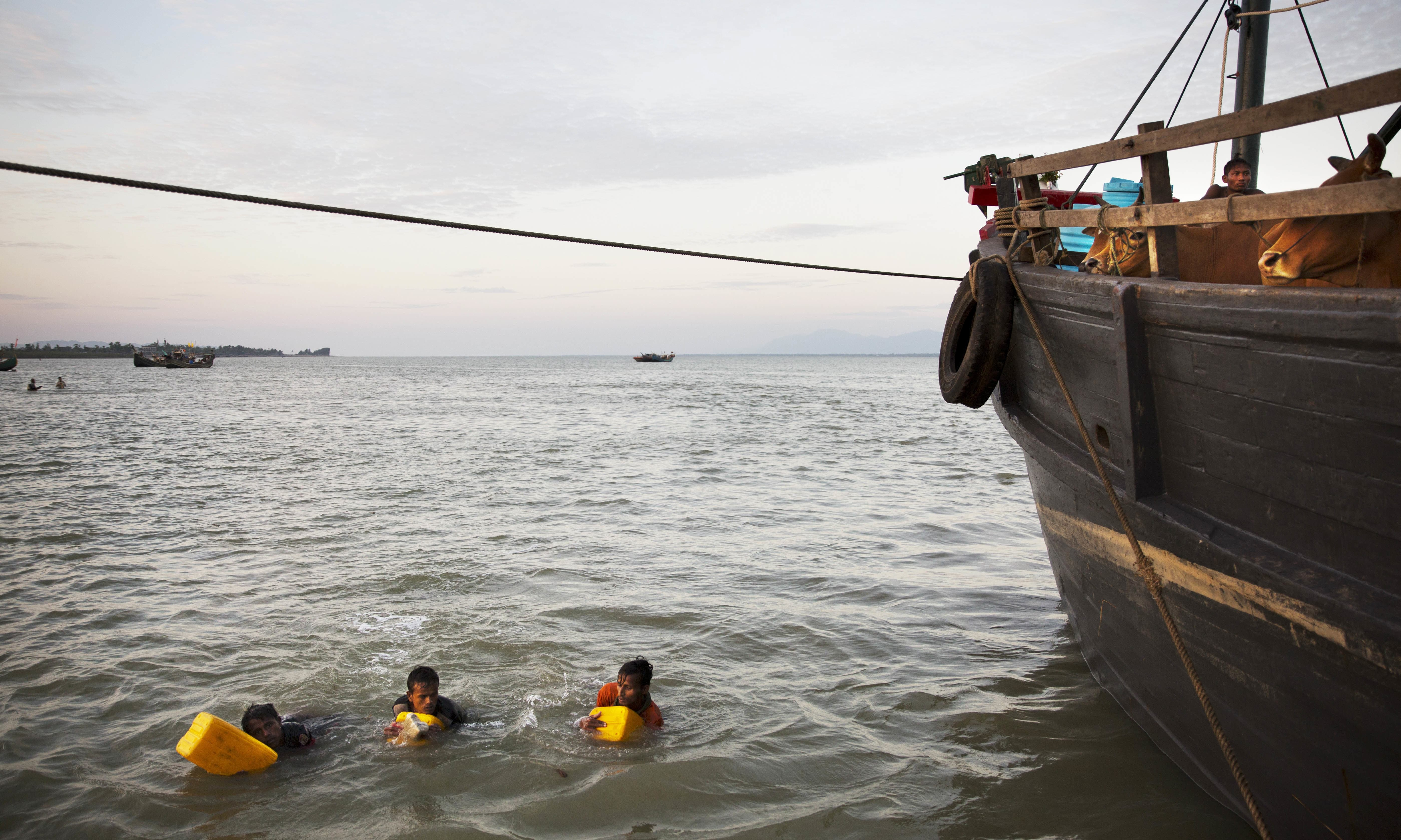 In this Nov. 4, 2017, photo, Rohingya Muslims use yellow plastic drums as flotation devices as they arrive at Shah Porir Dwip, Bangladesh, after swimming the Naf river. —AP