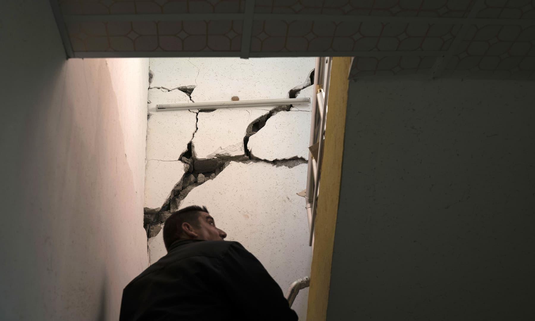 شمالی عراق کے شہر دربندیخاں میں تباہ کن زلزلے کے بعد ایک شخص ایک مخدوش گھر کا جائزہ لے رہا ہے۔ — فوٹو اے پی۔