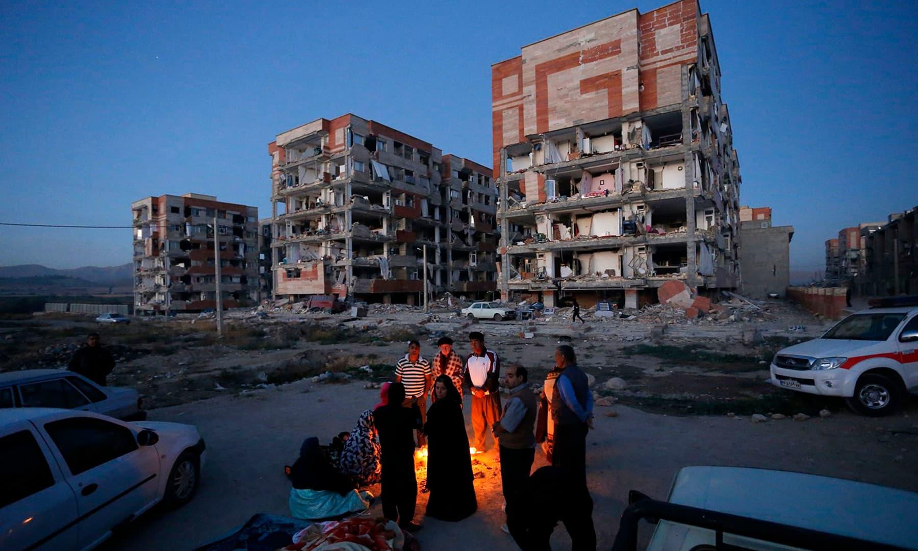 ایران کے صوبے کرمانشاہ کے علاقے سرپولِ ذہب میں زلزلہ متاثرین خود کو گرم رکھنے کے لیے آگ کے گرد جمع ہیں۔ — فوٹو اسنا/اے ایف پی۔