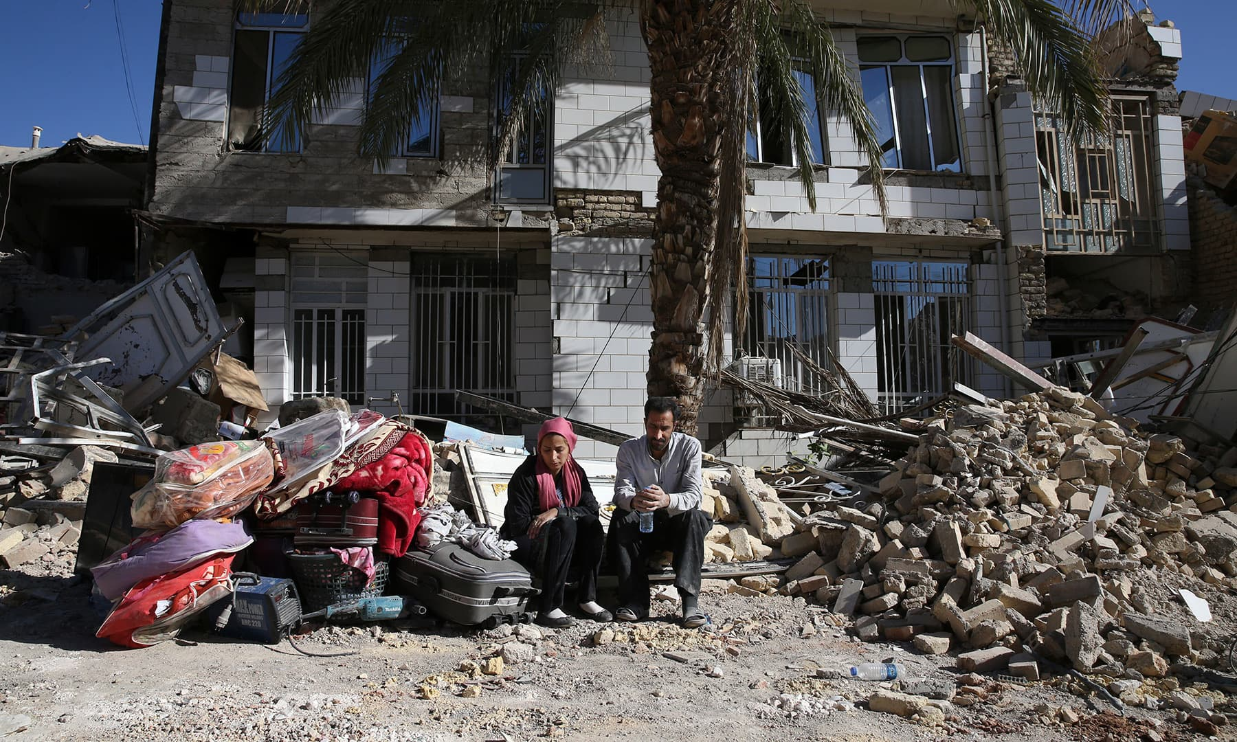 کرمانشاہ کے علاقے سرپولِ ذہب میں زلزلہ زدگان سڑک پر بیٹھے ہیں۔ — فوٹو اے پی۔