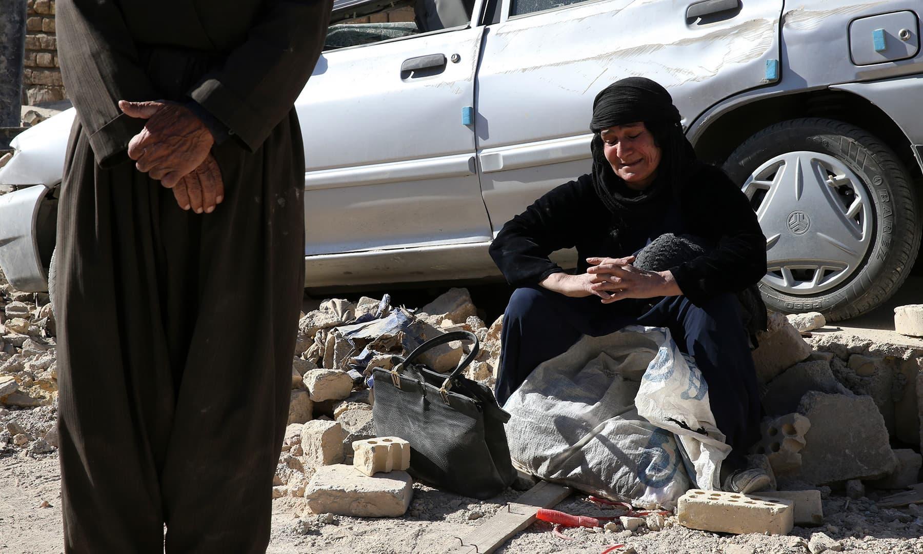 کرمانشاہ میں زلزلے سے متاثر ایک خاتون ملبے پر بیٹھی ہیں۔ — فوٹو اے پی۔
