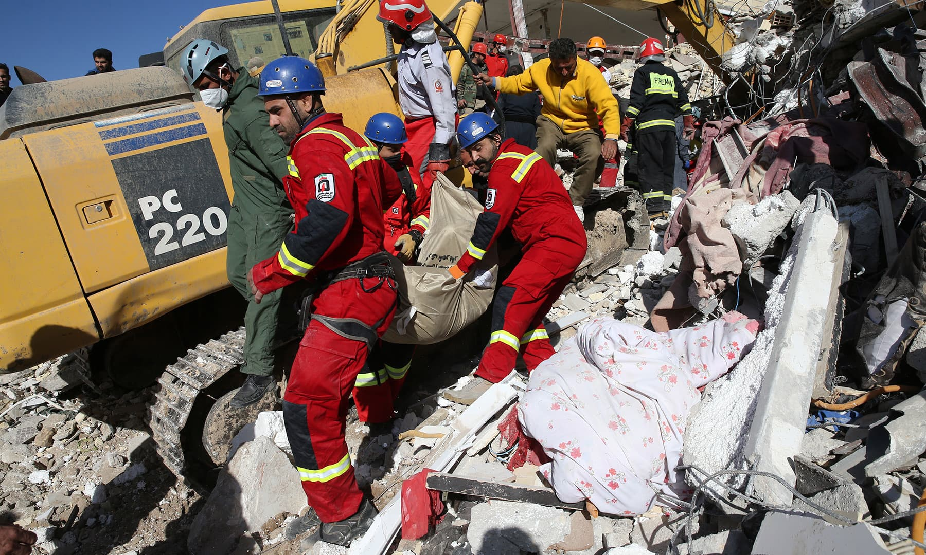 کرمانشاہ میں امدادی کارکن ملبے سے لاشیں نکال رہے ہیں۔ — فوٹو اے پی۔