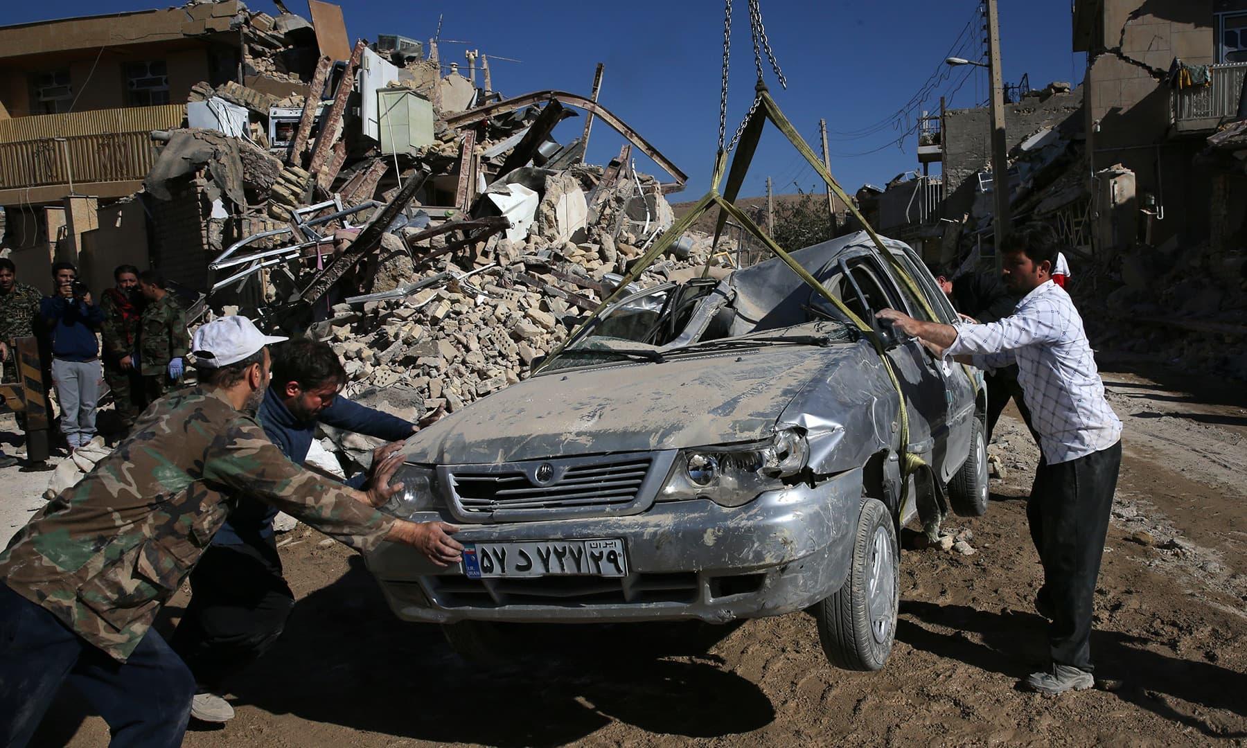 ایران کے صوبے کرمانشاہ کے علاقے سرپولِ ذہب میں ایک تباہ شدہ گاڑی کو کرین کے ذریعے ہٹایا جا رہا ہے۔ — فوٹو اے پی۔