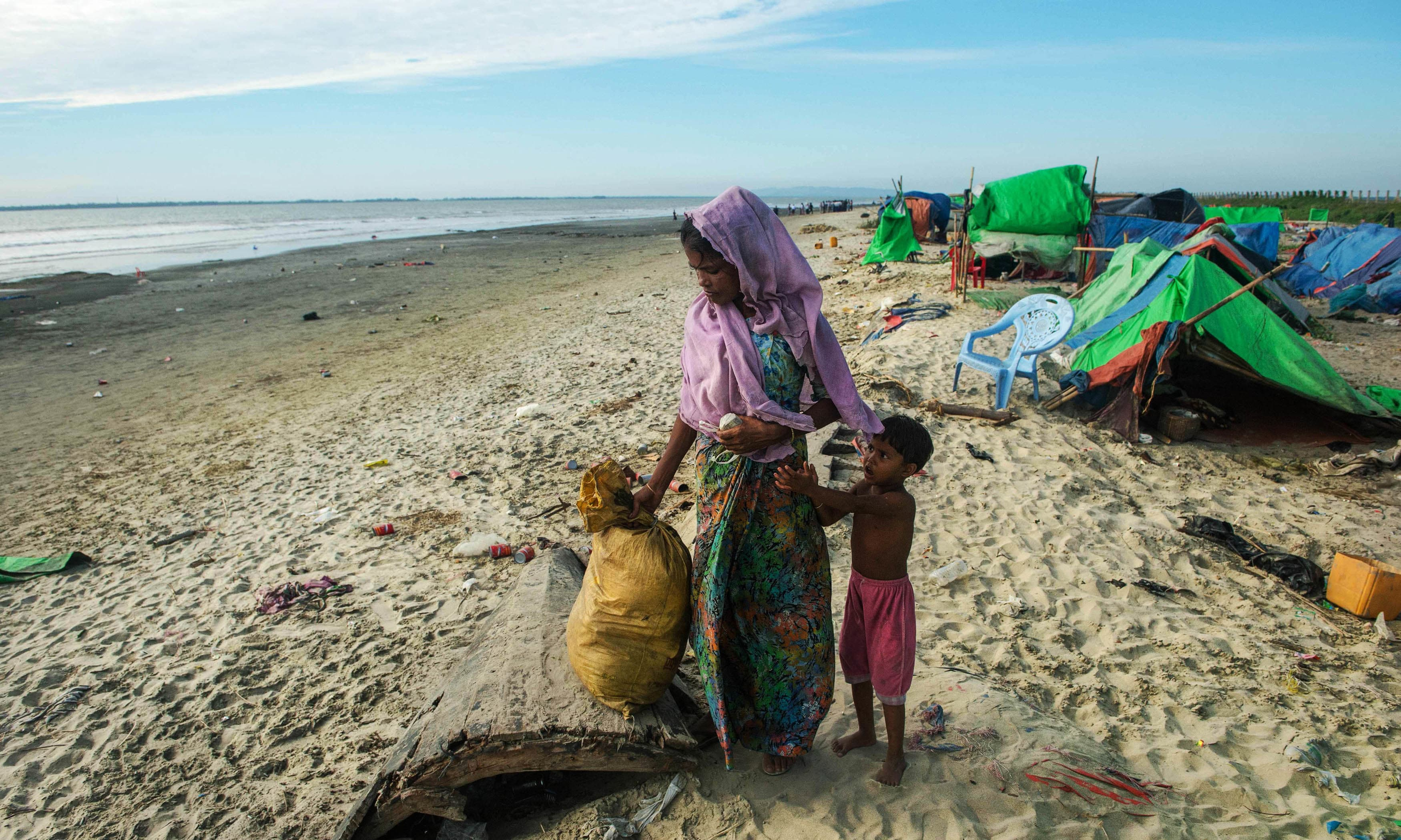 a woman who was carrying a bag on her head takes a break while holding onto a child near tents at a makeshift camp in Rakhine. —AFP