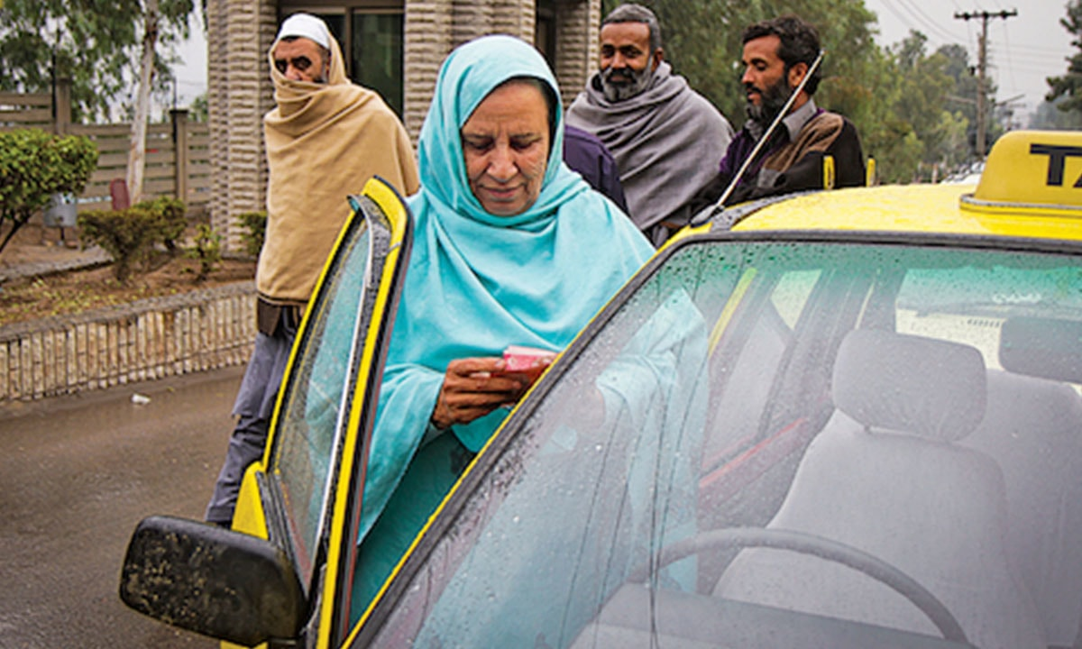 Zahida Kazmi, a taxi driver, gets into her yellow cab in Rawalpindi | Zayer Hassan/Reuters