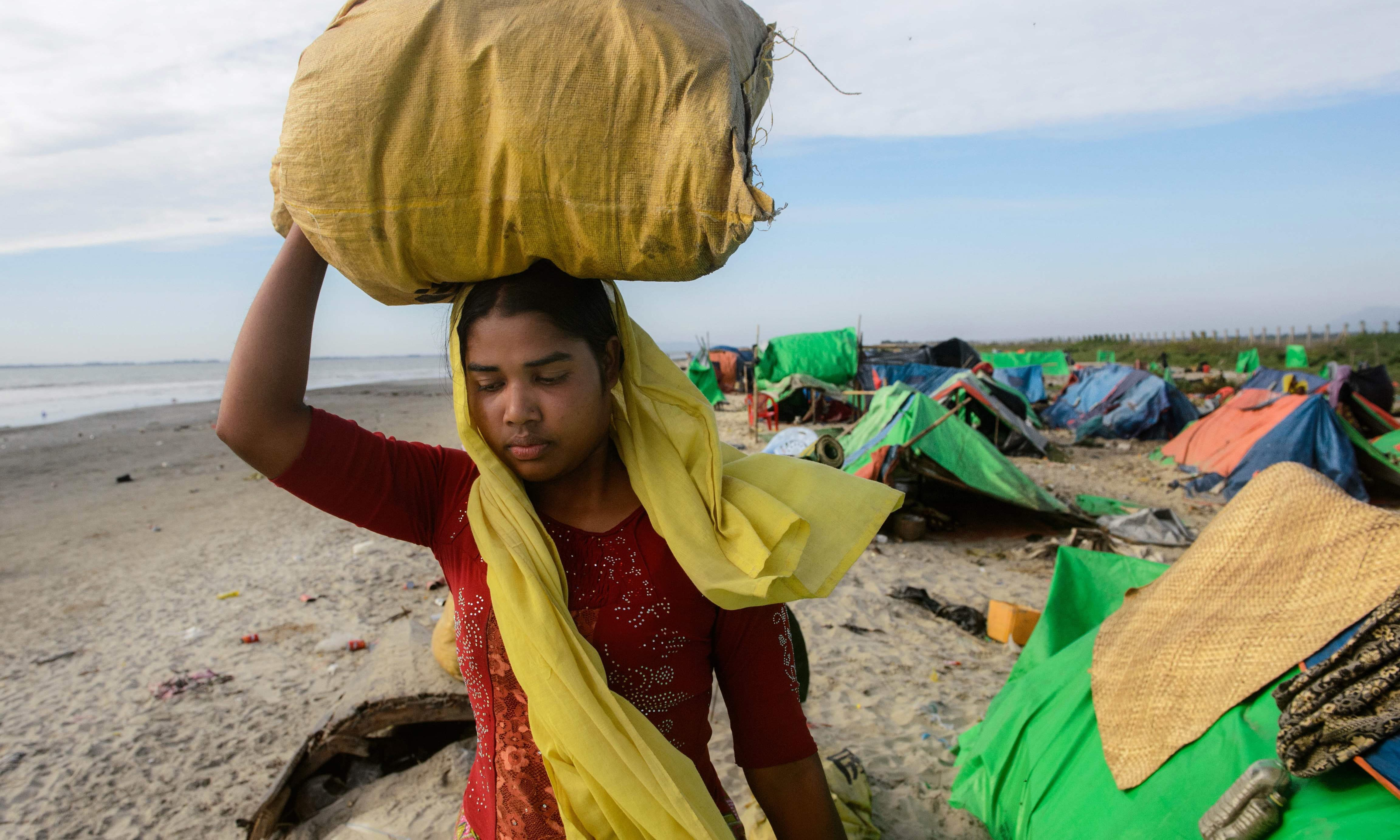 A woman carries a bag on her head as she walks near tents at a makeshift camp in Rakhine state in Myanmar, while waiting to find a way to cross over into Bangladesh. —AFP