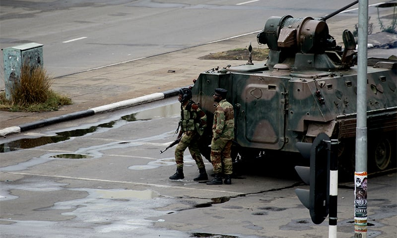 A military tank is seen with armed soldiers on the road leading to President Robert Mugabe's office in Harare, Zimbabwe. ─ AP