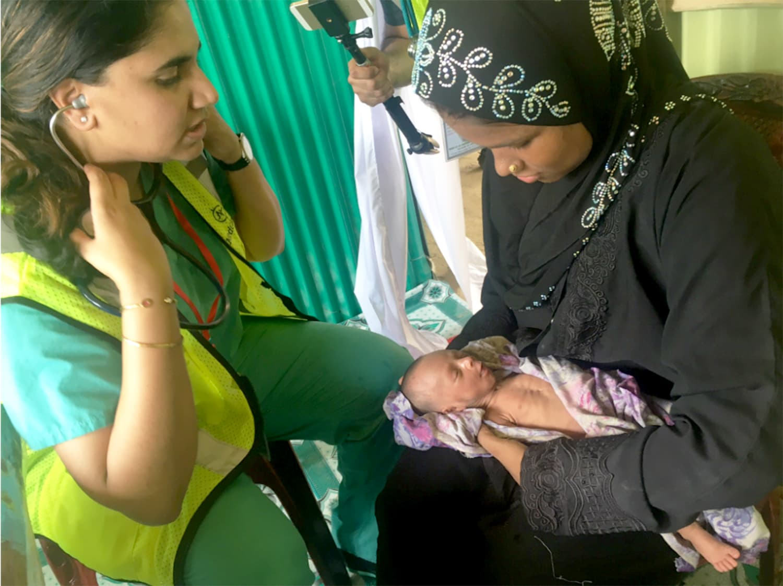 Dr. Minal Ahson examining a very small newborn.