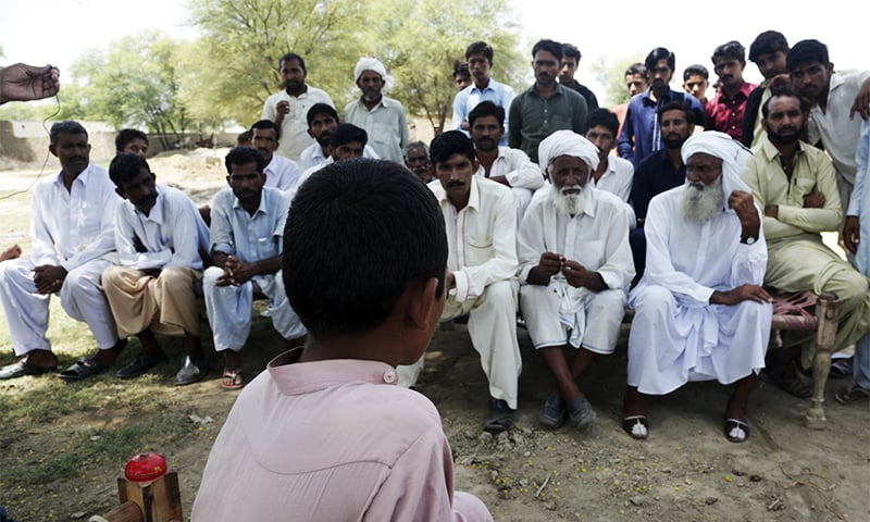 A Pakistani boy who was allegedly raped by a cleric sits before villagers in Vehari. ─ AP