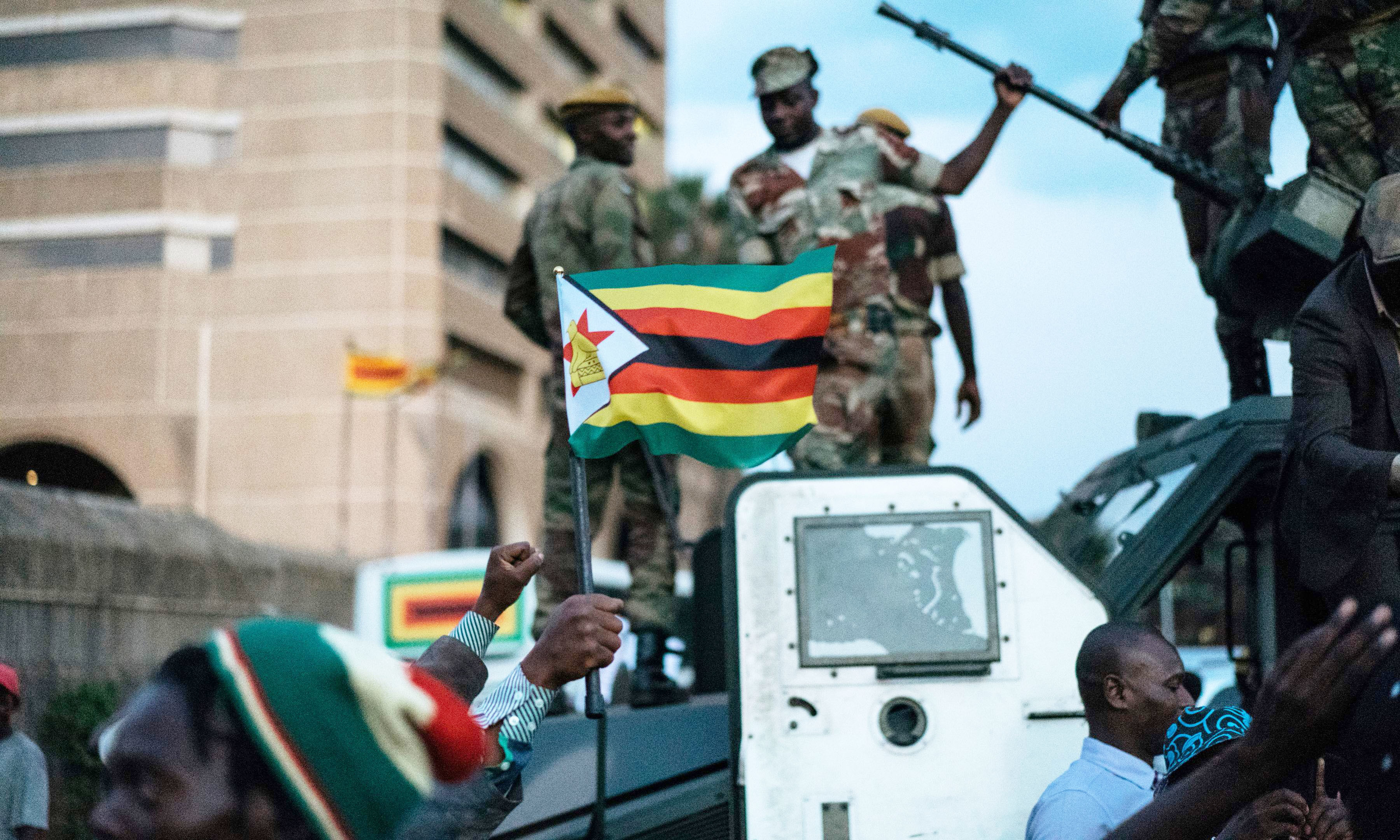 A man holds up the national flag of Zimbabwe as Zimbabwean soldiers are celebrated by citizens in the streets in Harare, on November 21, 2017 after the resignation of Zimbabwe's president Robert Mugabe. —AFP