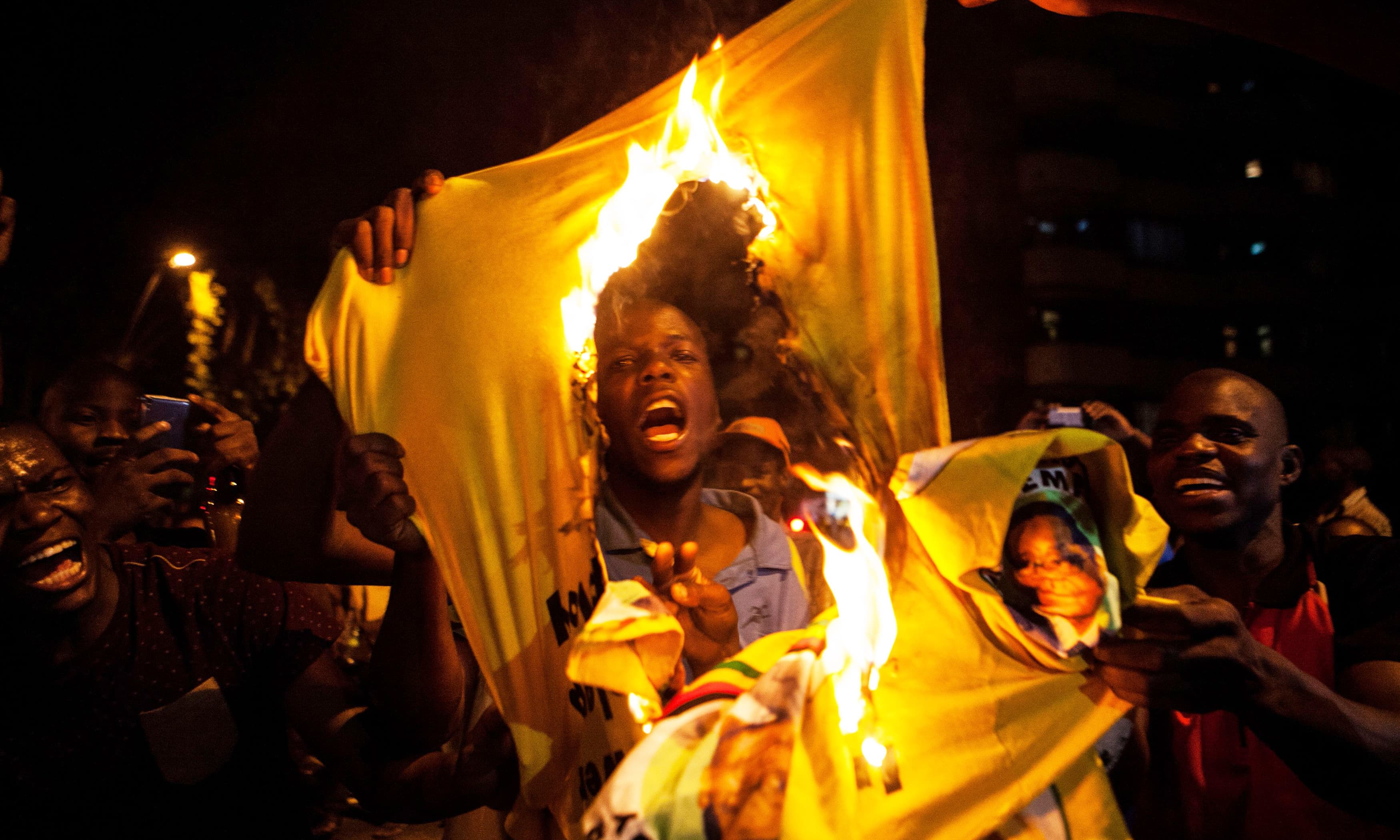A Zimbabwean national burns a shirt of Zimbabwe's ruling party, the Zimbabwe African National Union Patriotic Front (ZANU PF), as hundreds of Zimbabweans living in South Africa celebrate the resignation of Zimbabwe's president Robert Mugabe in the streets of the district of Hillbrow in Johannesburg. —AFP
