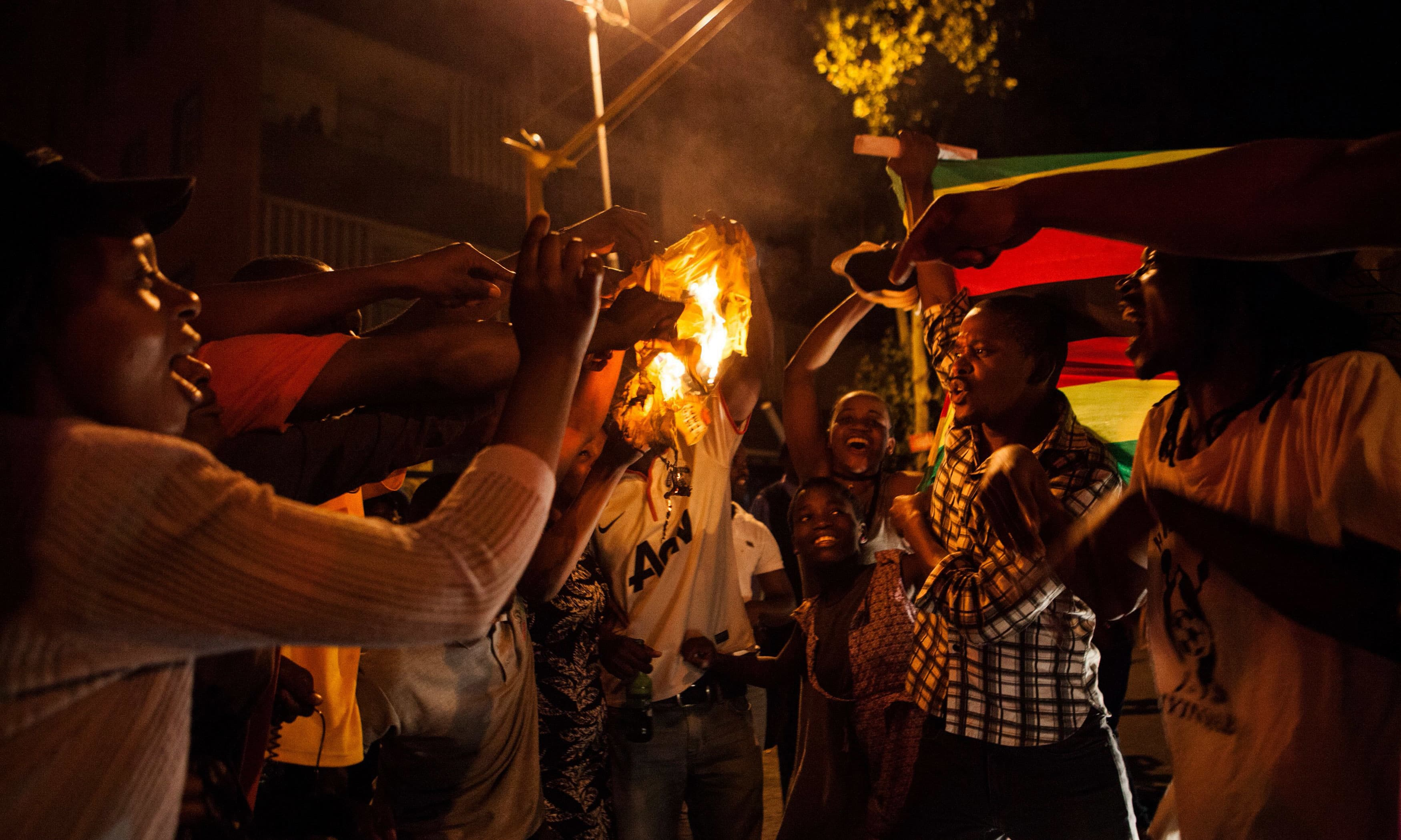 Zimbabwean nationals burn a shirt of Zimbabwe's ruling party, the Zimbabwe African National Union Patriotic Front (ZANU PF). —AFP
