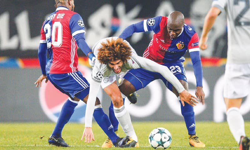 BASEL: Manchester United's Marouane Fellaini (C) vies for the ball with FC Basel's Geoffroy Serey Die (L) and Eder Balanta during their Group 'A' match at St Jakob Park.—AFP