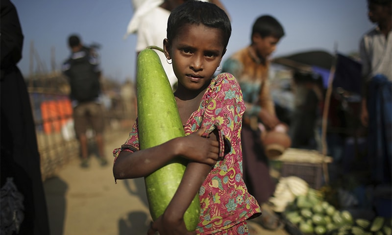 A Rohingya Muslim girl carries a vegetable from the market on the outskirts of Kutupalong refugee camp on Tuesday in Bangladesh.— AP