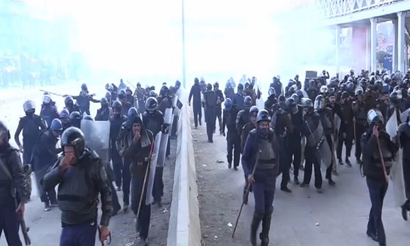 Security officials not wearing masks can be seen affected by the tear gas.— DawnNews