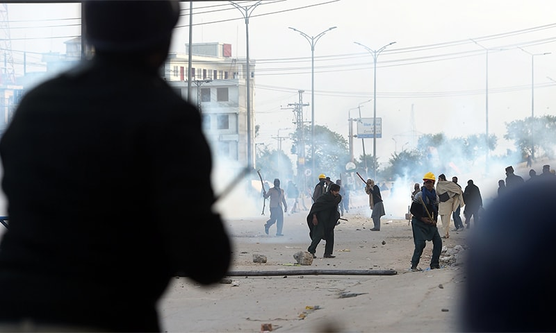Activists of Tehreek Labbaik Ya Rasool Allah throw rocks toward riot police.— AFP