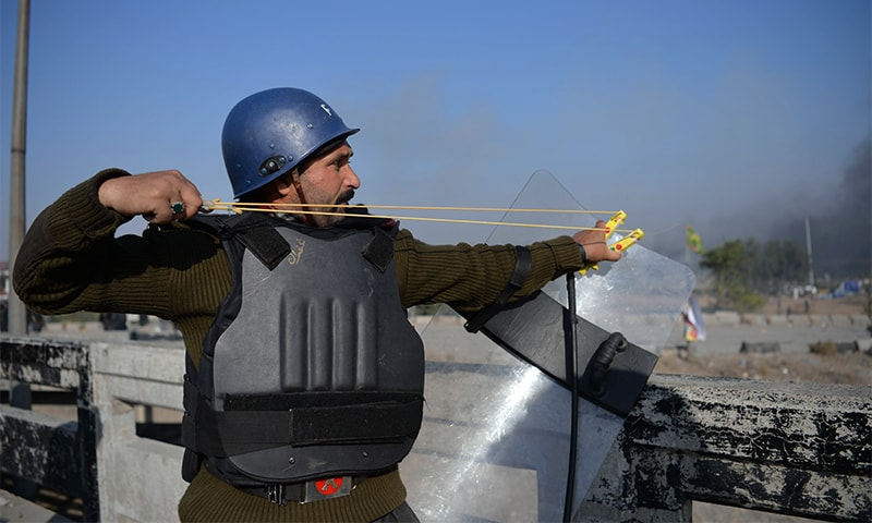 A policeman uses a slingshot during clashes with protesters in Islamabad.— AFP