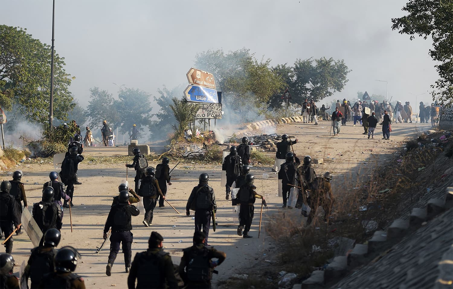 Policemen in riot gear chase protesters from the Tehreek-i-Labaik Yah Rasool Allah during a clash. ─ AFP