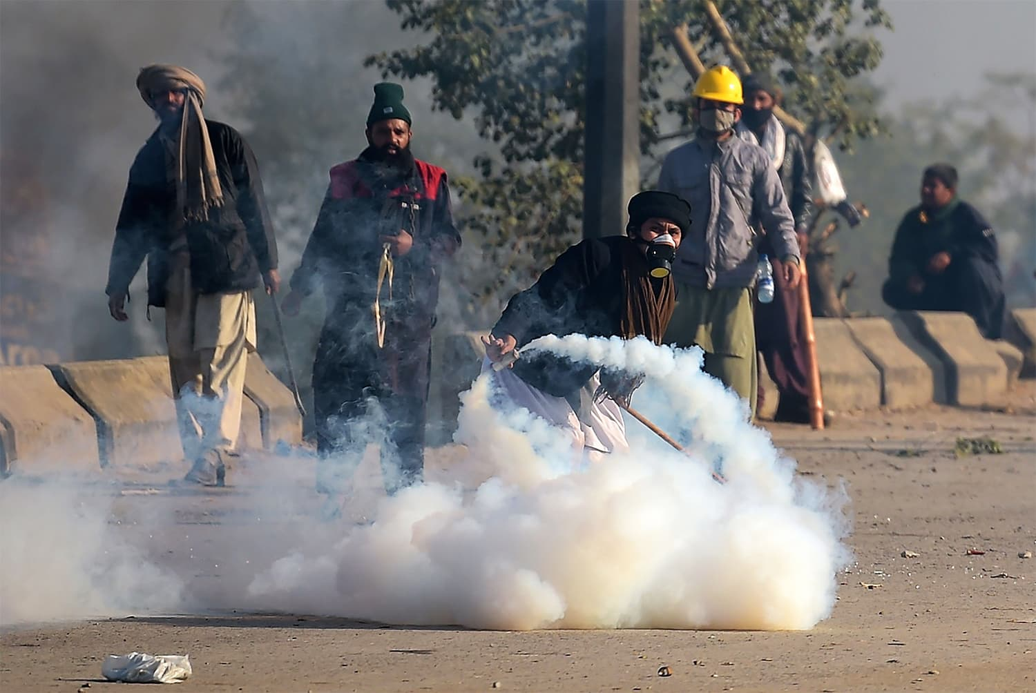 A TLY protester throws a tear gas shell back towards police during a clash in Islamabad. ─ AFP