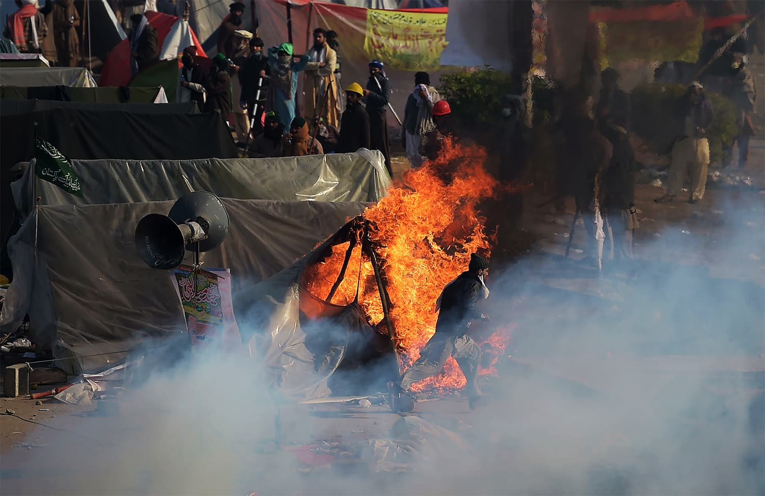 A TLY protester runs past a burning tent during a clash with police in Islamabad. ─ AFP