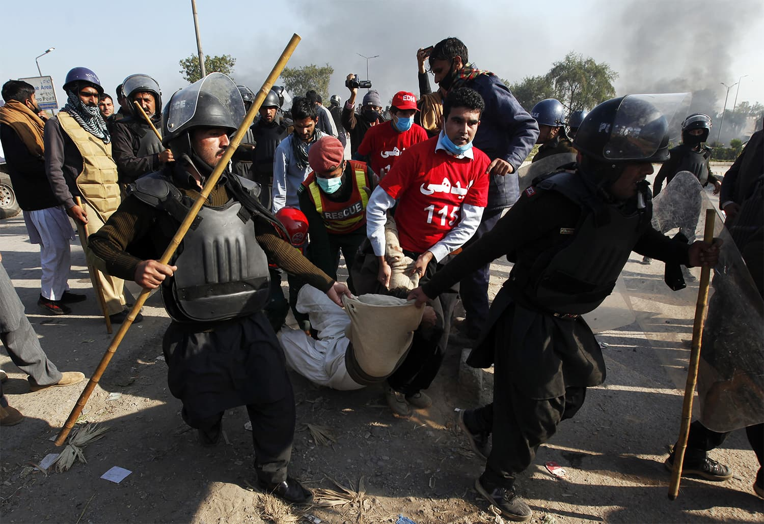 Police officers carry an injured protester during a clash in Islamabad. ─ AP