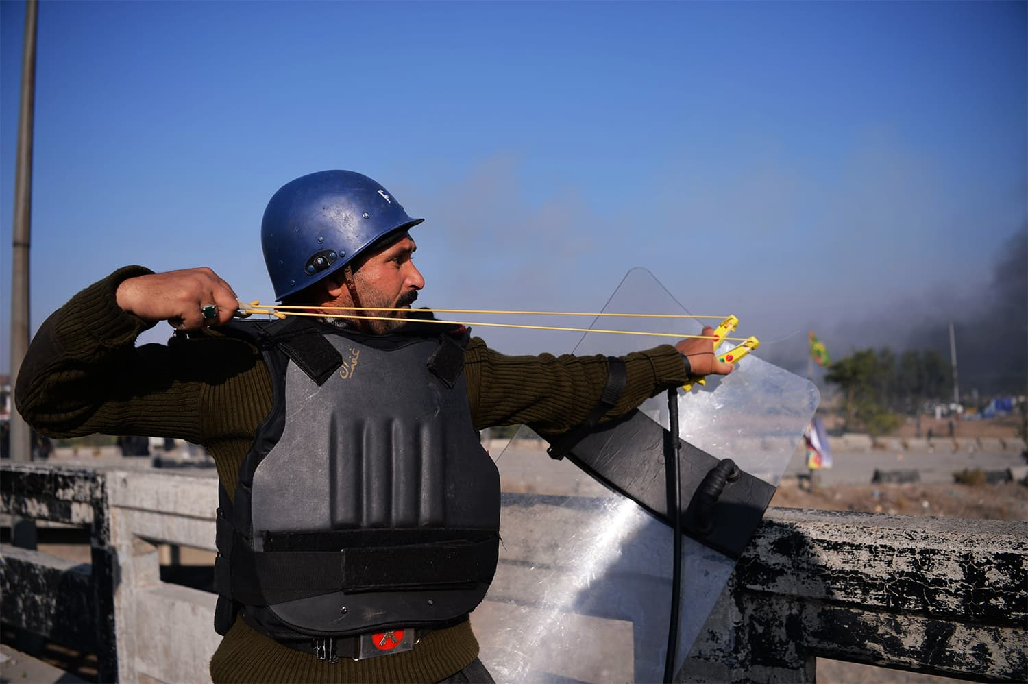A policeman uses a slingshot during clashes with TLY protesters. ─ AFP