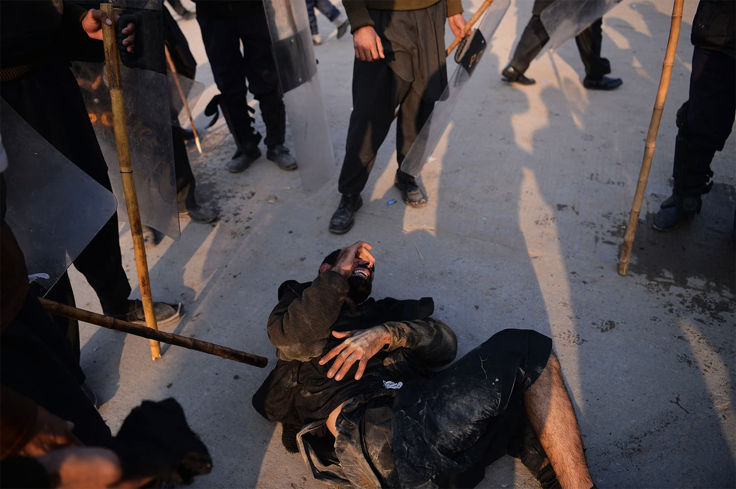 Riot policemen gather around an injured TLY protester in Islamabad. ─ AFP
