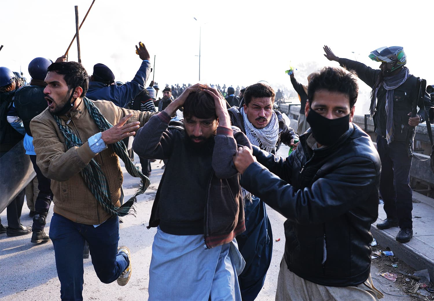Plainclothes policemen arrest an injured TLY activist (C) during a clash in Islamabad. ─ AFP