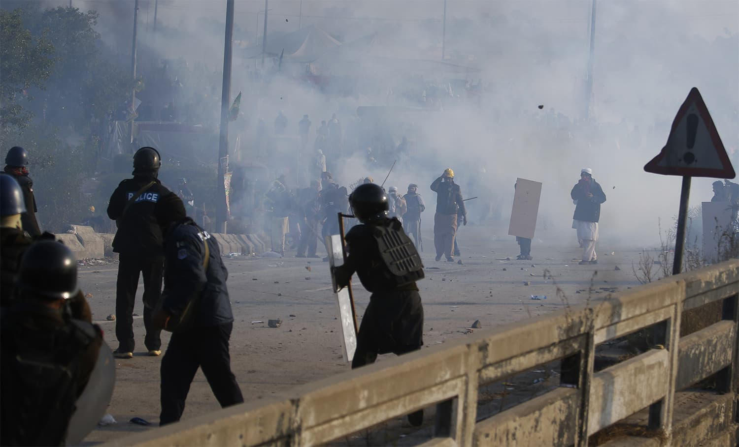 Protesters and police officers throw stones each others during a clash in Islamabad. ─ AP