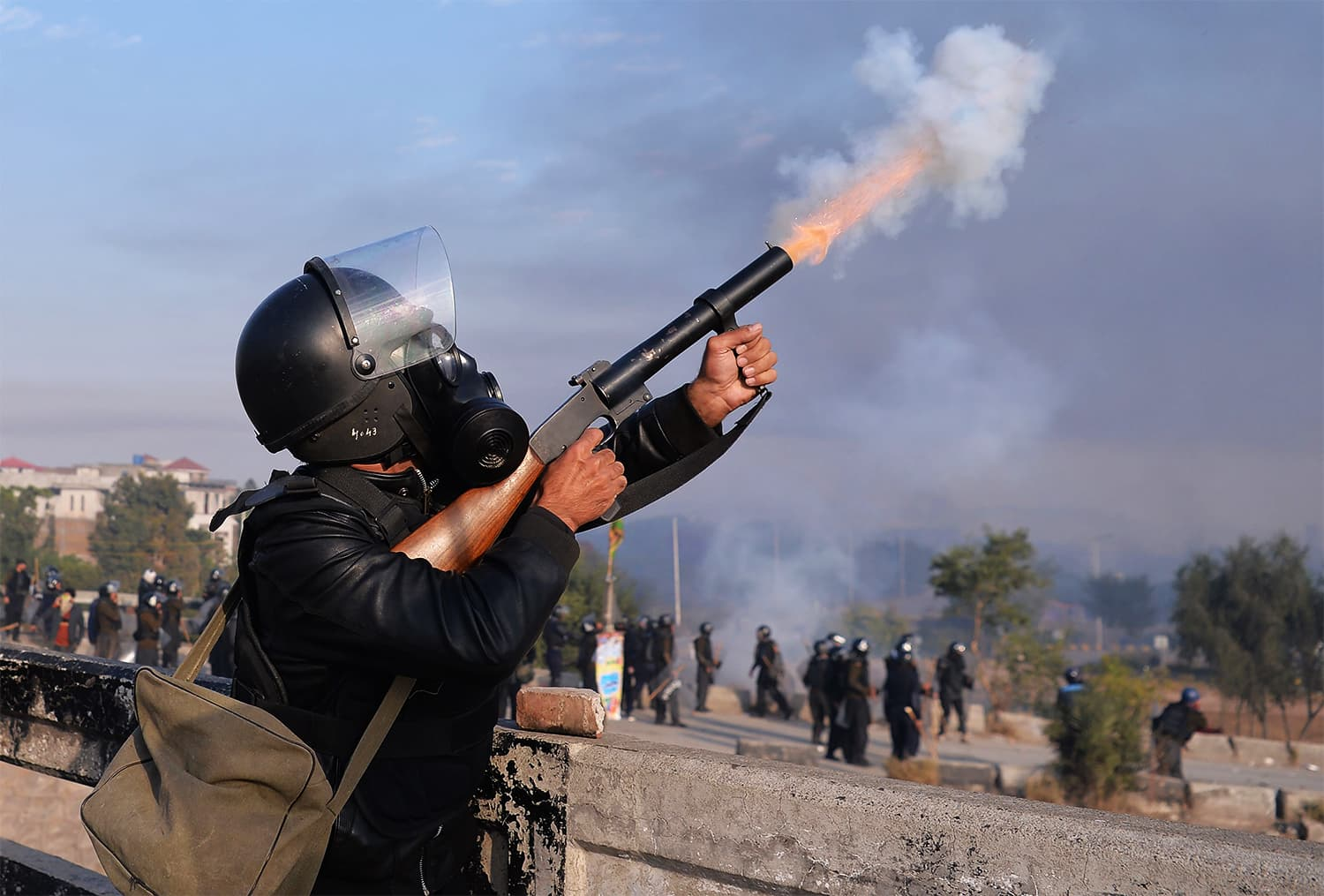 A policeman fires at TLY protesters during clashes in Islamabad. ─ AFP