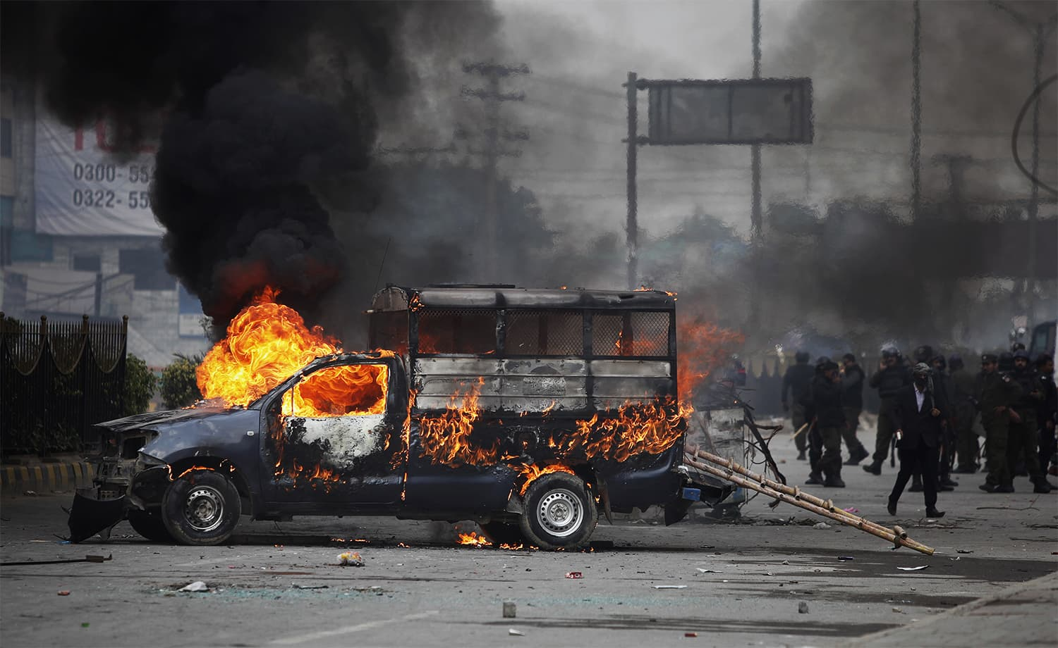 Police officers gather next to a burning police vehicle setting on fire by protesters during a clash in Islamabad. ─ AP