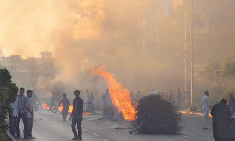 PROTESTERS light bonfires on the arterial Sharea Faisal on Saturday; (right) demonstrators block the Superhighway near Al Asif Square.—Online / Faysal Mujeeb / White Star