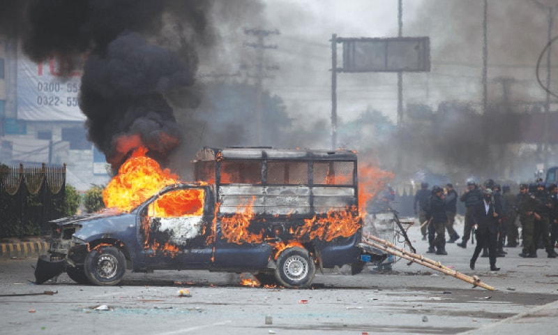 Islamabad: Policemen gather next to a burning police vehicle set on fire by protesters during a clash on Saturday.—AP