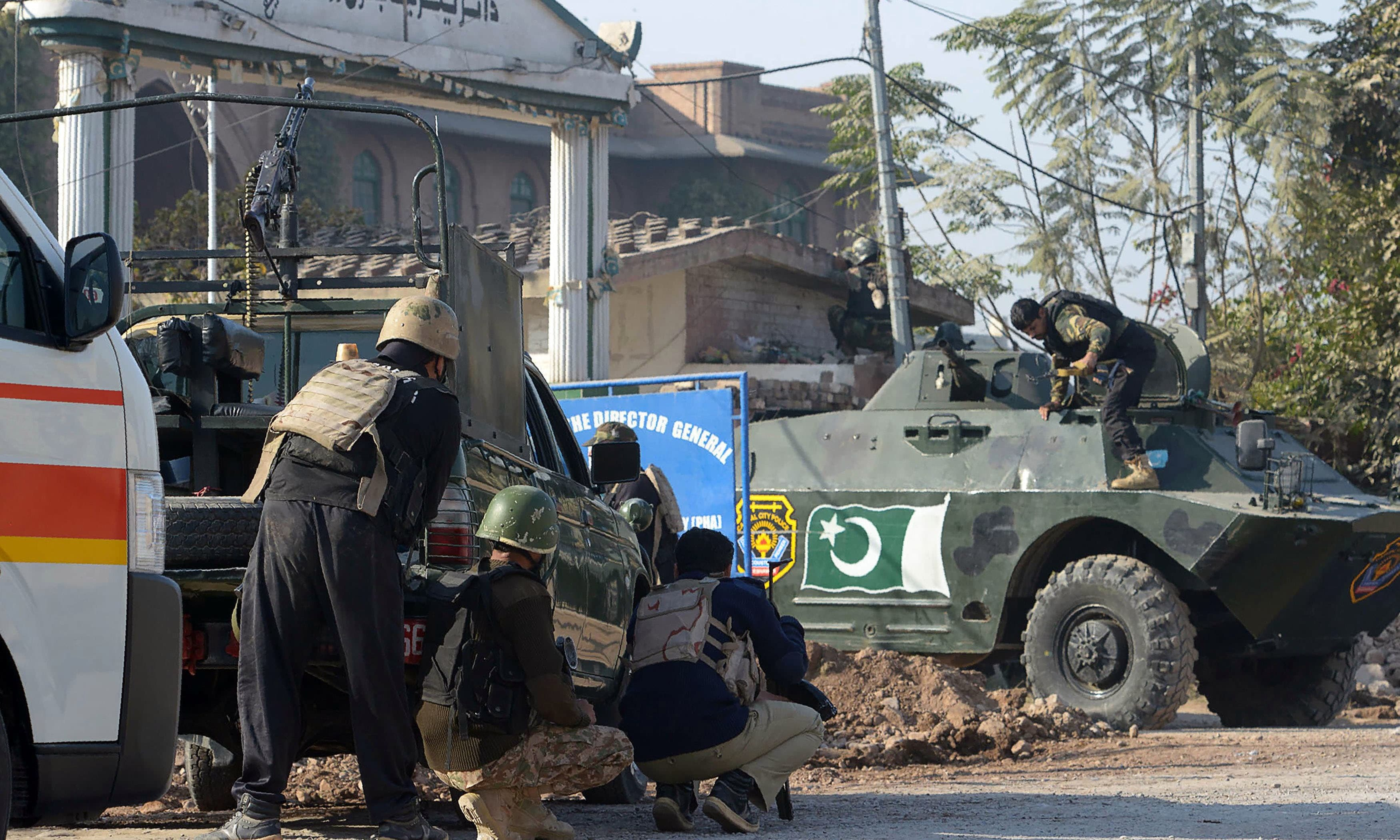Security personnel take position outside Peshawar's Agricultural Training Institute after a terror attack. — AFP