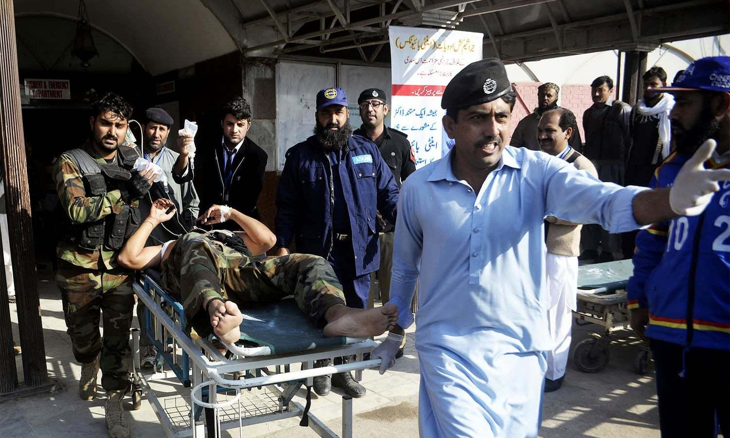 Staff rush security personnel injured during the operation to a hospital. ─ AP
