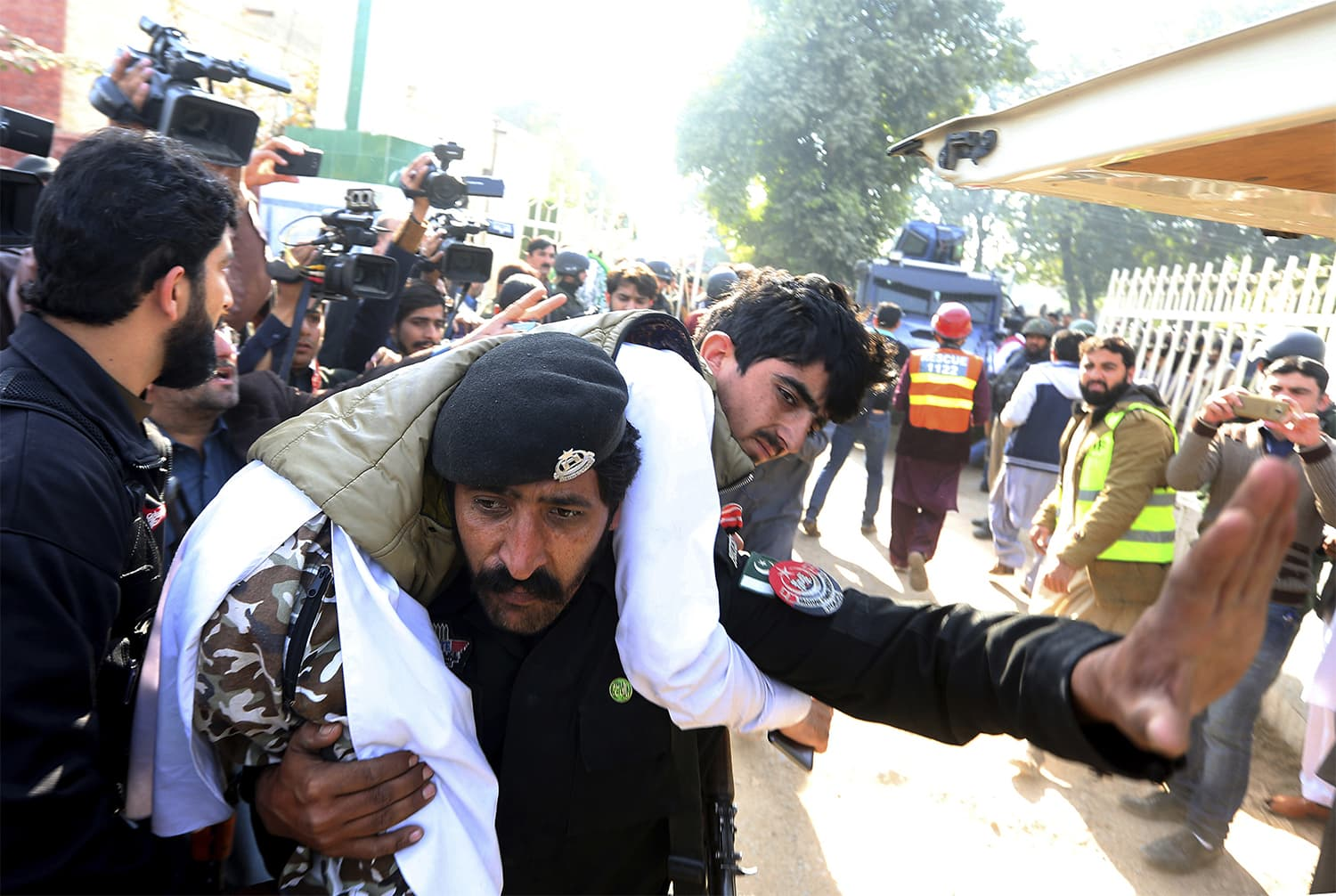 A security officia carries an injured man to an ambulance at the site of the attack. ─ AP