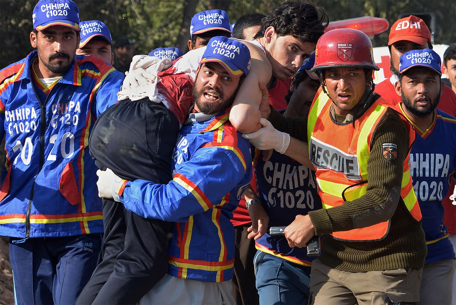 Rescue officials carry an injured student away from the ATI after the attack. ─ AFP