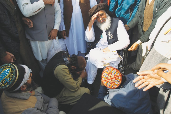 A supporter prays at the feet of Rizvi| Caren Firouz/Reuters