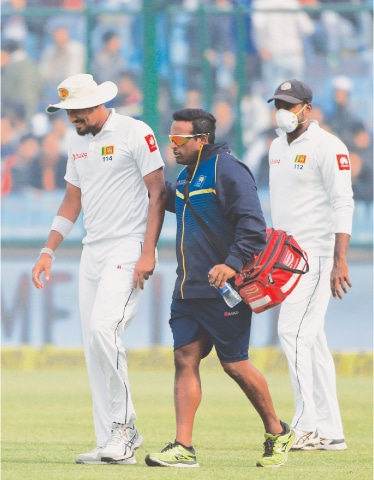 SRI LANKA'S Suranga Lakmal (L) walks off the field after he vomited during the fourth day of the third Test against India.—AP