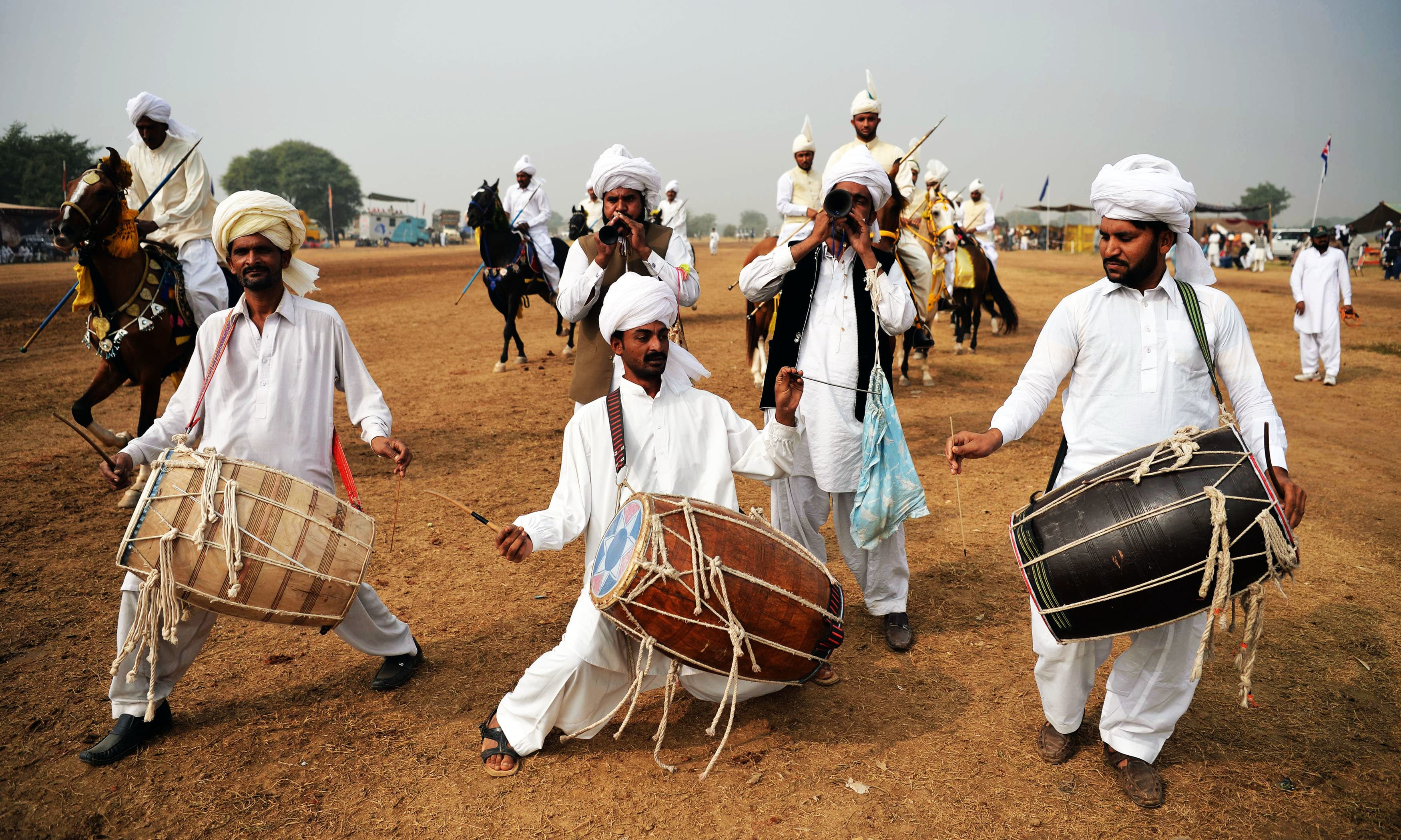 Traditional drummers perform at a tent-pegging competition during an annual festival at the village of Kot Fateh Khan in Attock. —AFP