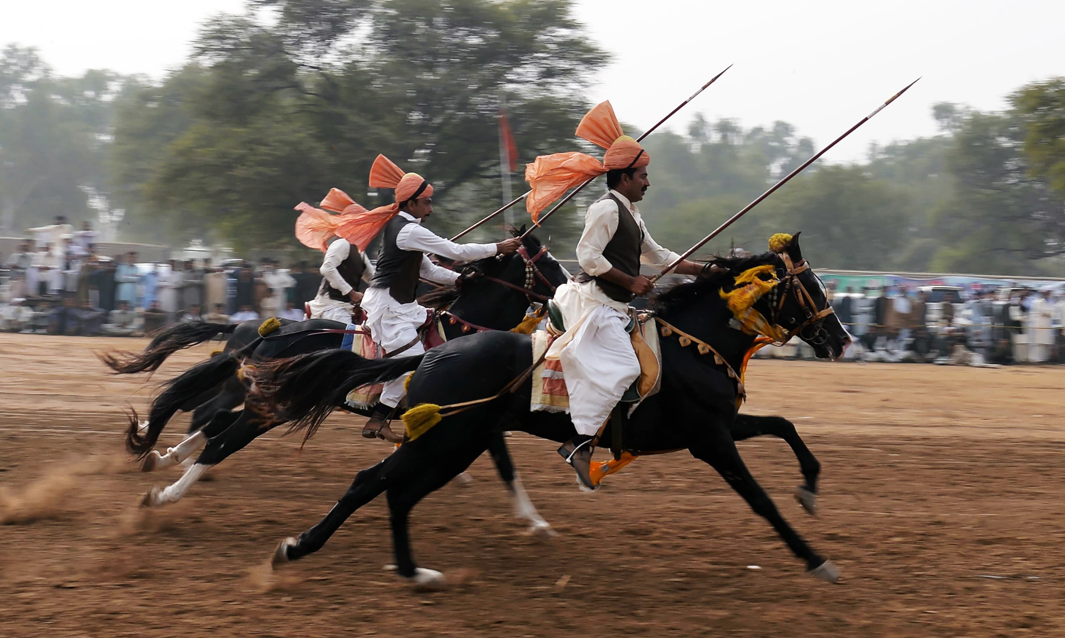 Horse riders charge across a course holding a lance to pick up pegs at a tent-pegging competition during an annual festival at the village of Kot Fateh Khan in Attock district. —AFP
