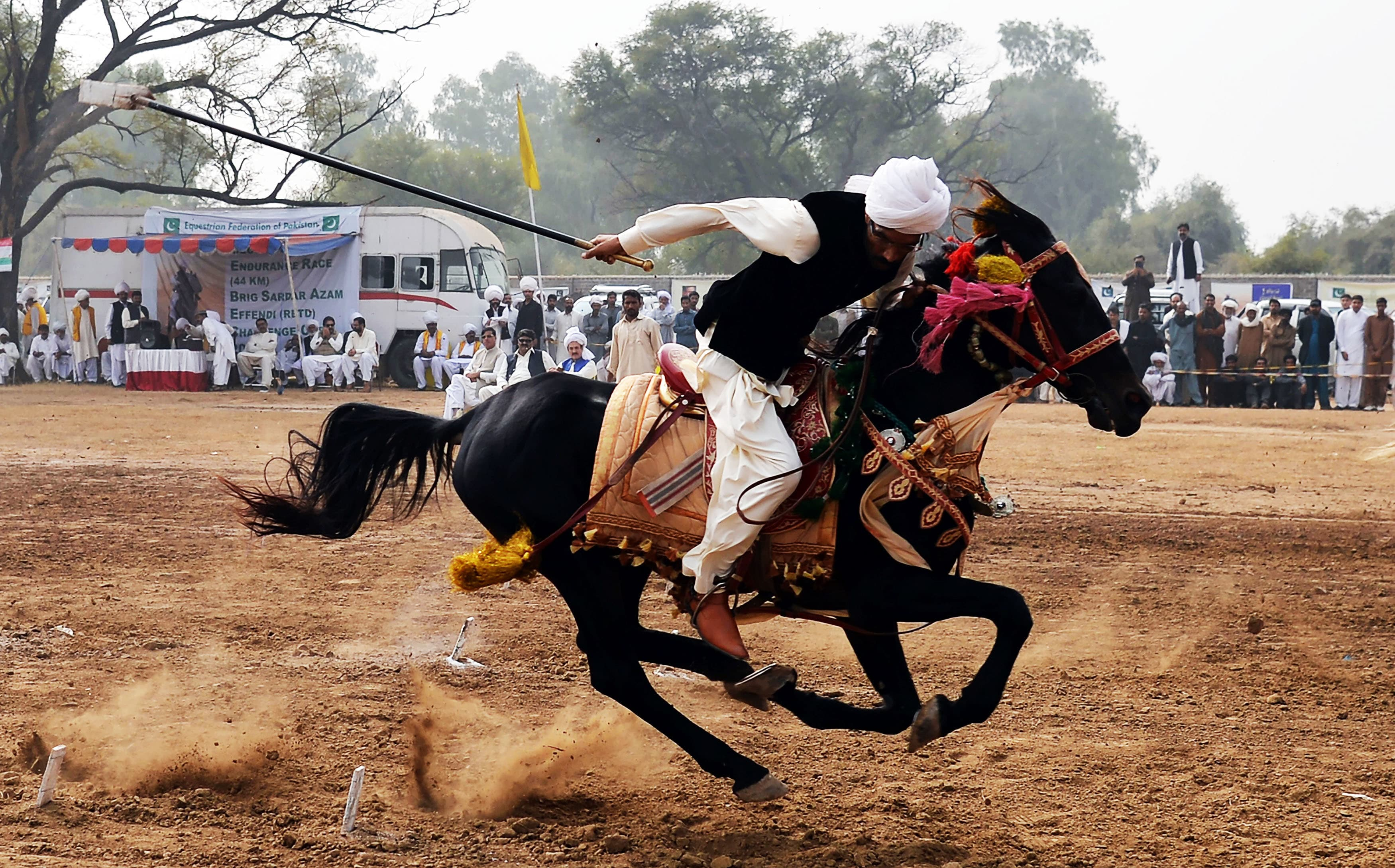 "This photograh taken on November 7, 2017, shows a Pakistani horse rider charging across a course holding a lance to pick up pegs at a tent-pegging competition during an annual festival at the village of Kot Fateh Khan in Attock district in Punjab province. Festooned with garlands and colourful bridles, turbaned riders mounted on horseback in full gallop lower their lances at tiny wooden blocks as they practice the centuries-old tradition of tent-pegging in Pakistan. / AFP PHOTO / AAMIR QURESHI / To go with ""Pakistan-lifestyle-equestrian-tradition,FEATURE"" by Khurram SHAHZAD — AFP or"