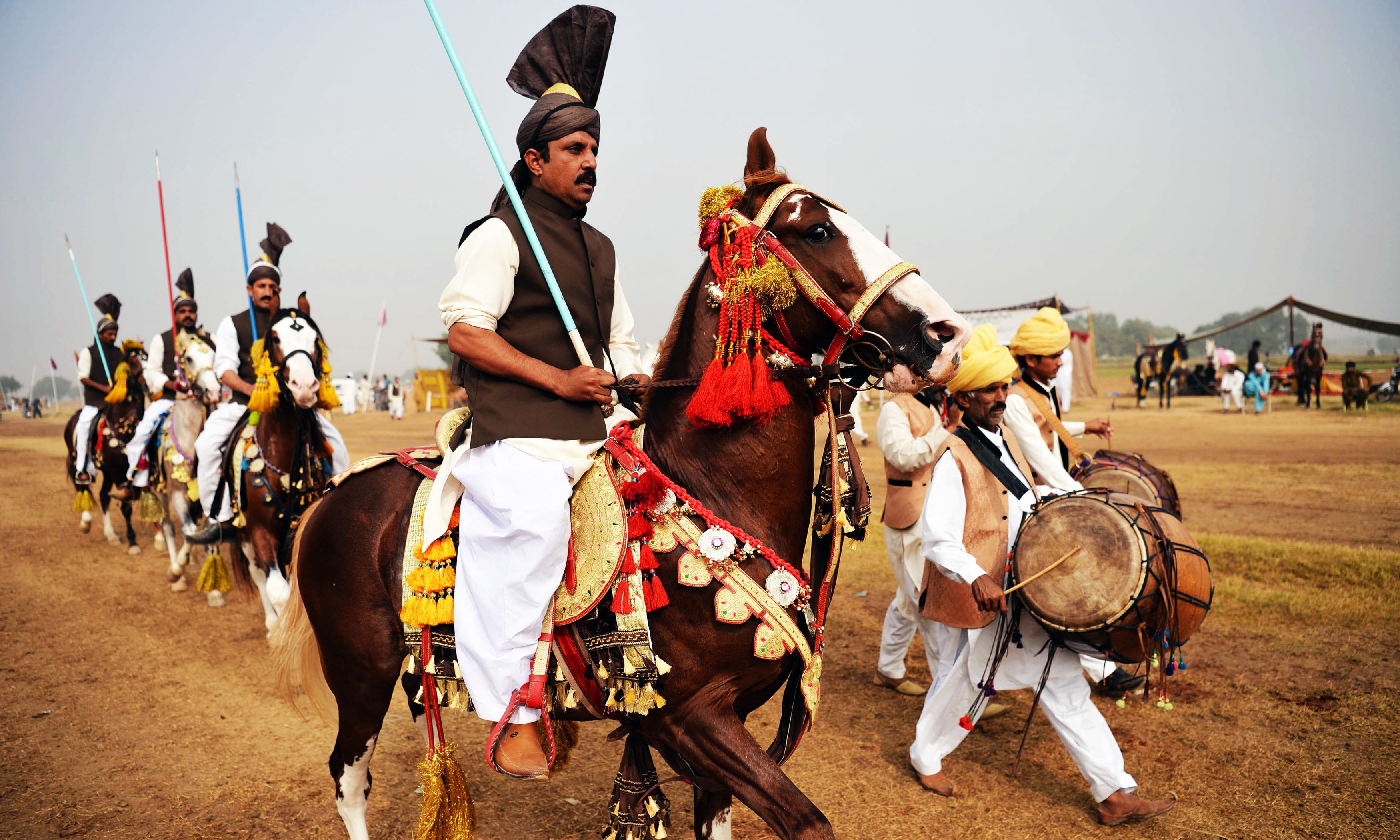 Riders hold lances used to pick up pegs at a tent-pegging competition in Attock district. —AFP